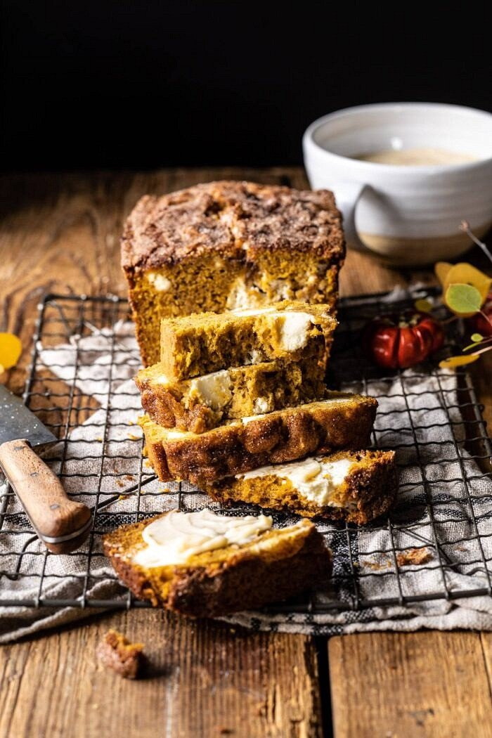 side angled photo of Cream Cheese Swirled Pumpkin Bread with multiple slices cut and stacked on top of each other