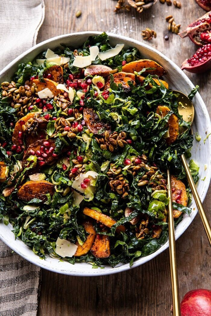 overhead photo of Fall Harvest Roasted Butternut Squash and Pomegranate Salad after being tossed with salad spoons in salad bowl