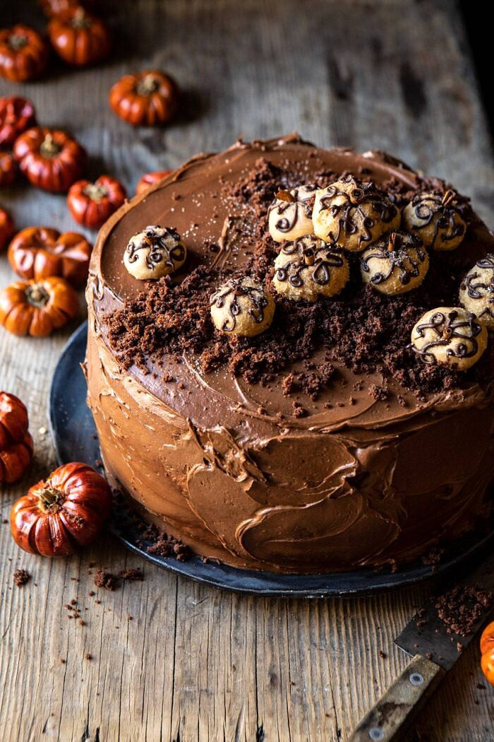 3/4 angle photo of Pumpkin Patch Chocolate Peanut Butter Cake with mini pumpkins on table