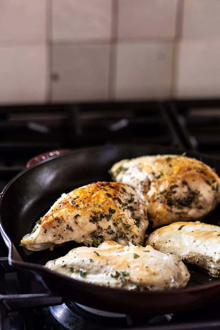 side angled photo of chicken cooking in skillet