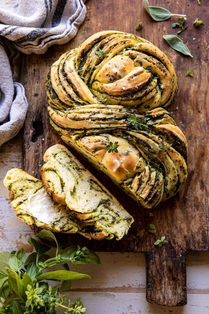 overhead photo of Swirled Garlic Herb Bread on cutting board with 2 pieces sliced
