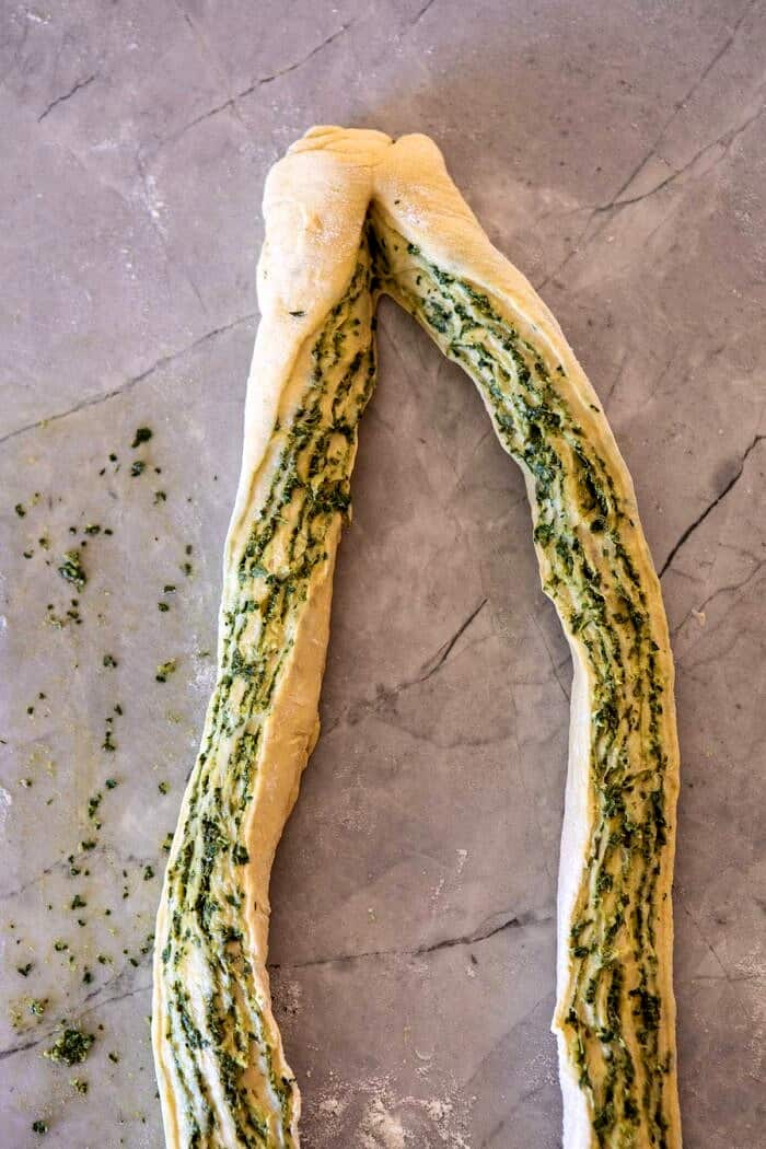 dough log sliced in half and twisted to show the inside before braiding