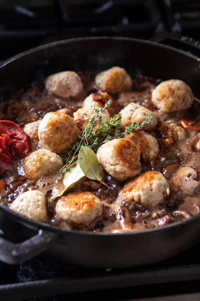 side angle photo of adding meatballs to skillet