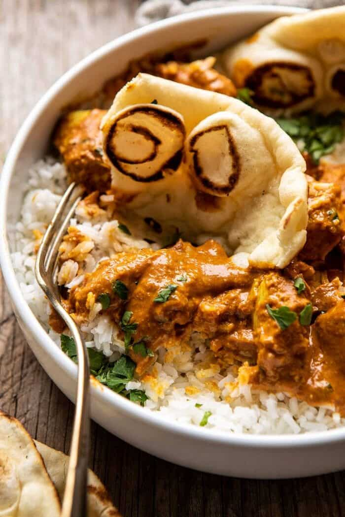 side angled close up photo of Super Simple Coconut Chicken Tikka Masala with fork in bowl