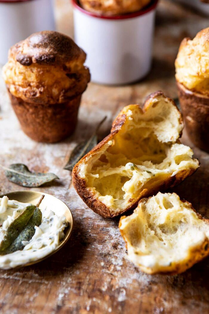front on close up photo of Parmesan Popovers with Crispy Sage Garlic Butter broken in half to show the airy inside of the popover