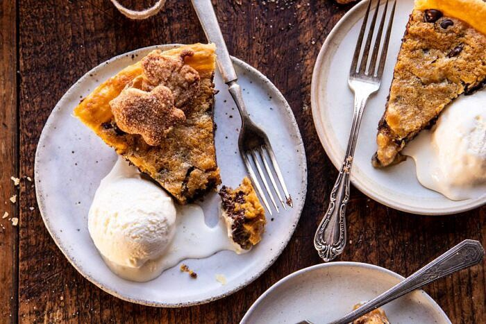 horizontal photo of Gooey Chocolate Chip Cookie Pumpkin Pie slices with ice cream on plates