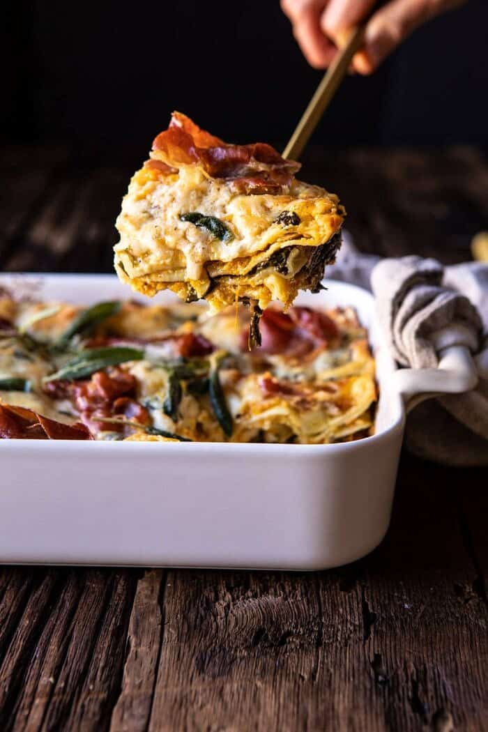 side angled photo of Roasted Butternut Squash and Spinach Lasagna with serving of lasagna being removed from dish