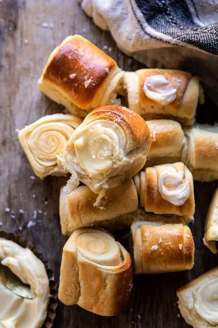 overhead close up photo of Salted Honey Butter Parker House Roll with butter on roll