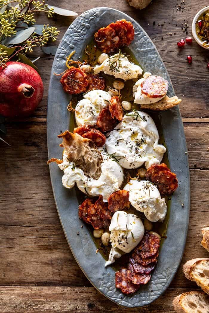 overhead photo of Burrata with Lemon Pepper Salami Bites on serving plate with pomegranate on table