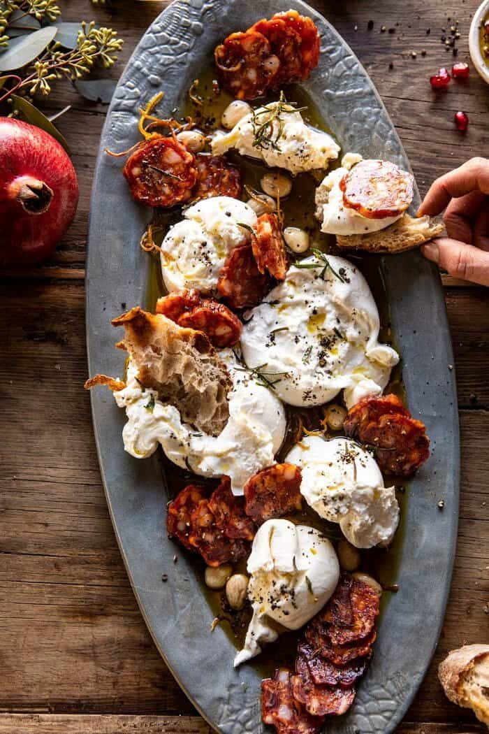 overhead photo of Burrata with Lemon Pepper Salami Bites and hand taking some of the cheese off the platter