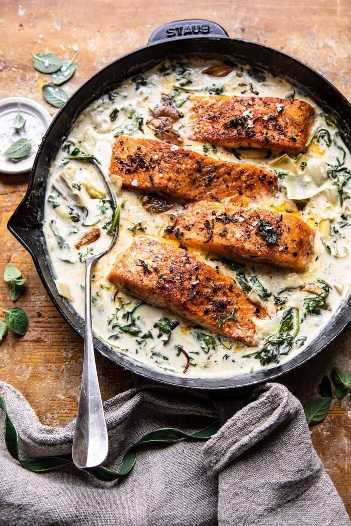 overhead photo of Creamy Spinach and Artichoke Salmon in skillet with spoon in sauce