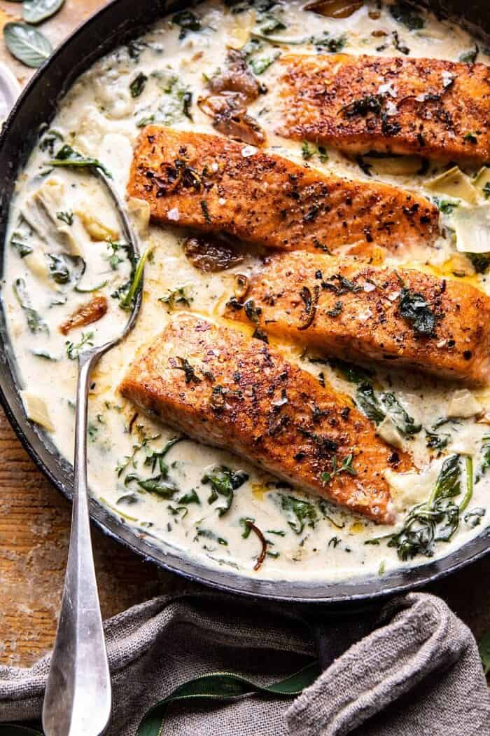 overhead close up photo of Creamy Spinach and Artichoke Salmon in skillet