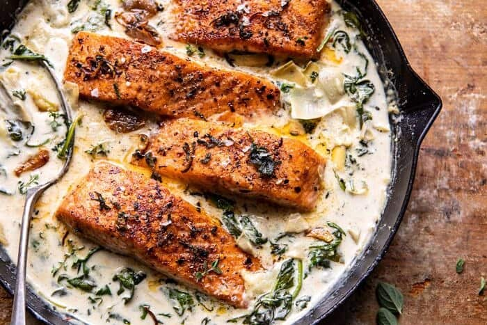 overhead horizontal photo of Creamy Spinach and Artichoke Salmon in skillet