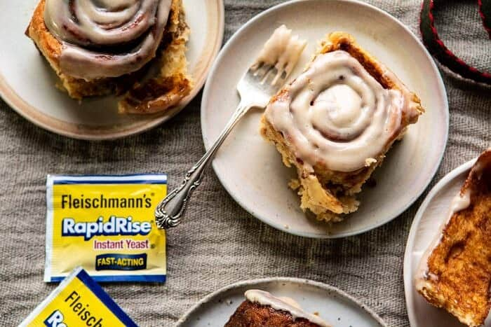 horizontal photo of Easy Gingerbread Brioche Cinnamon Rolls on plates with forks