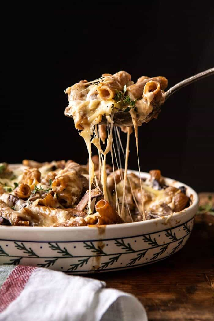 side angled photo of One Pot Creamy French Onion Pasta Bake with serving spoon pulling pasta out of the baking dish