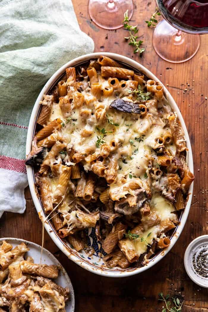overhead photo of One Pot Creamy French Onion Pasta Bake with serving of pasta removed and sitting on a plate next to dish