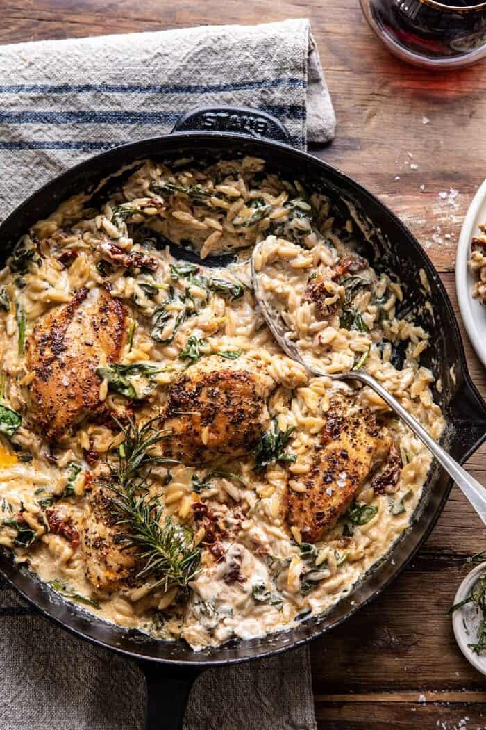 overhead photo of One Skillet Creamy Sun-Dried Tomato Chicken and Orzo with spoon in skillet