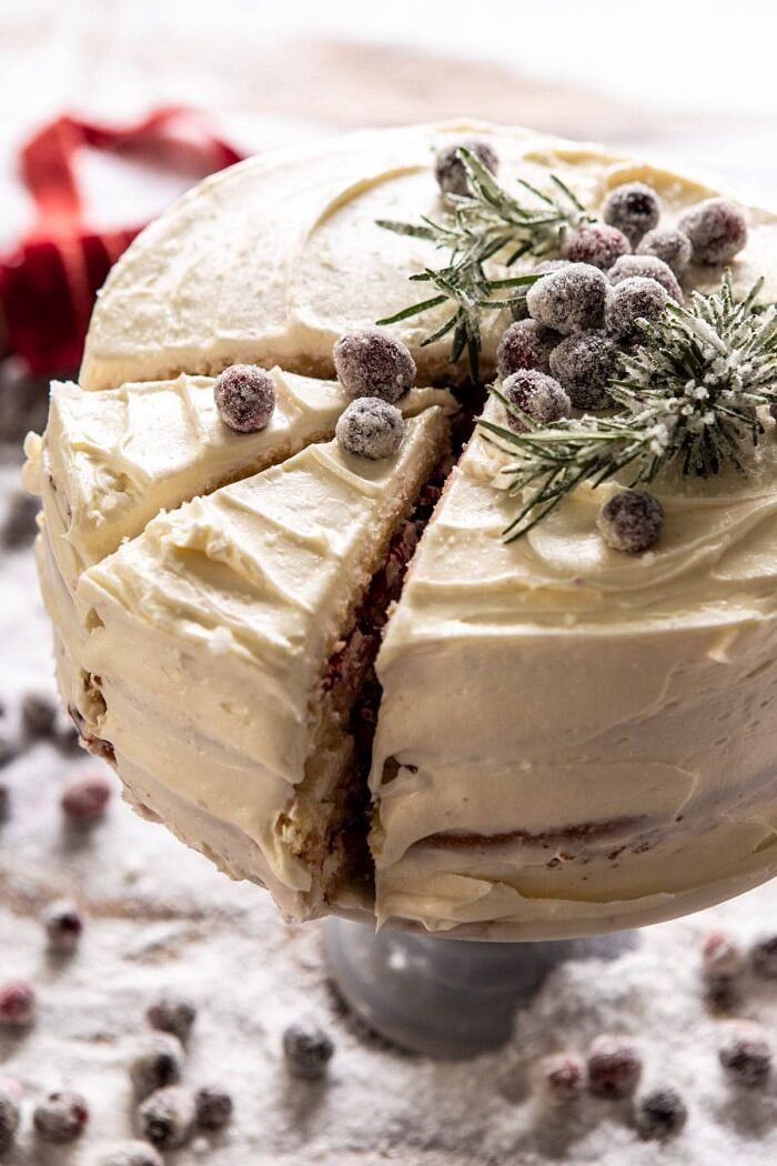 side angled close up photo of White Christmas Cranberry Layer Cake with 2 slices cut in cake