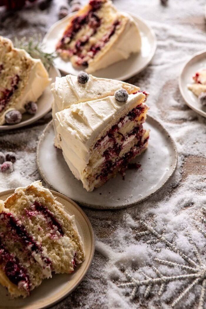 side angled photo of White Christmas Cranberry Layer Cake slices stand up on dessert plate