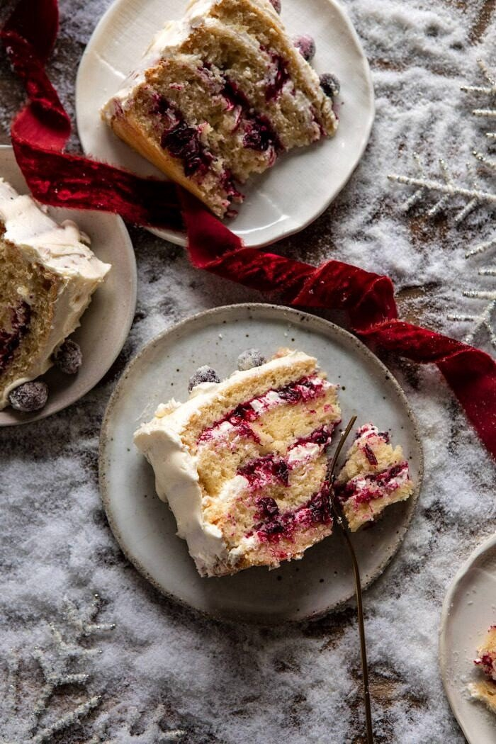 overhead close up photo of White Christmas Cranberry Layer Cake slice with fork in cake slice