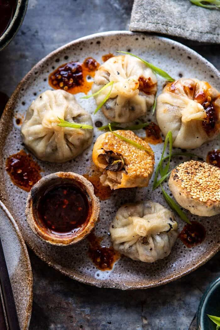 overhead photo of Chinese Mushroom Dumplings with Sweet Chili Ginger Sesame Sauce and bite taken out of dumpling