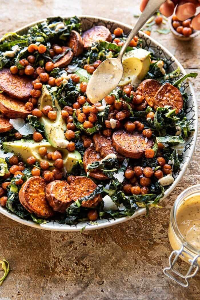 side angled photo of Kale Caesar Salad with Sweet Potatoes and Crispy Chickpeas with spoon drizzling dressing over salad