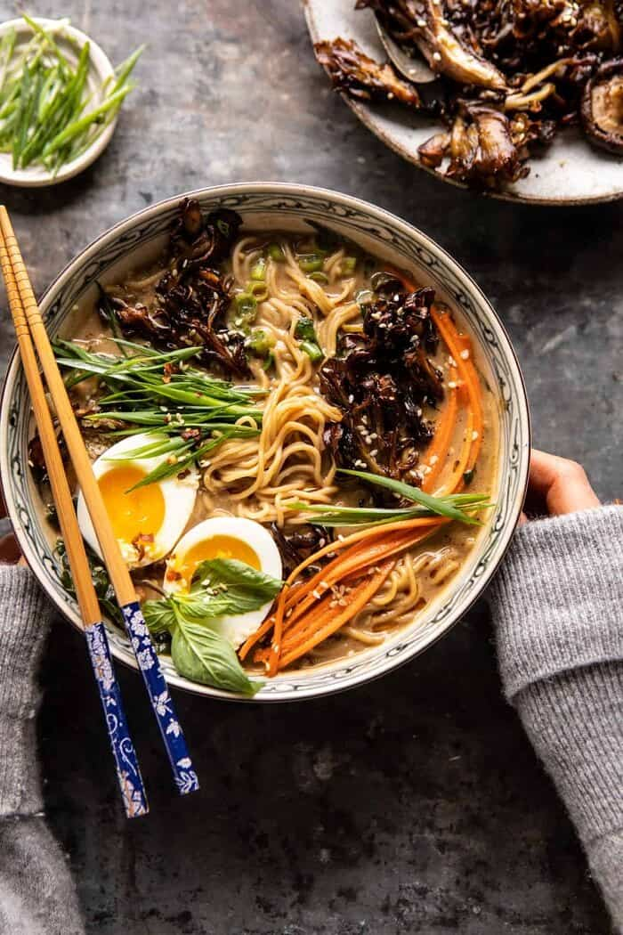 overhead photo of 30 Minute Creamy Sesame Miso Ramen with Crispy Mushrooms with hands on soup bowl