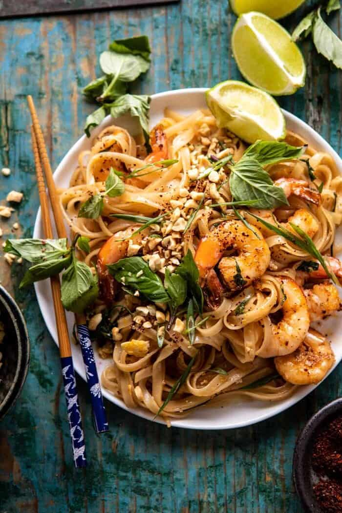 overhead close up photo of Better Than Takeout Garlic Butter Shrimp Pad Thai with chopsticks on the side of plate
