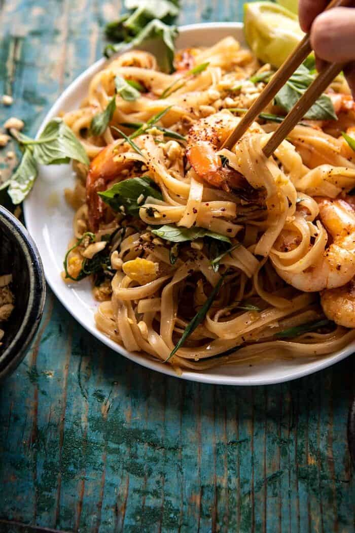side angled photo of Better Than Takeout Garlic Butter Shrimp Pad Thai with chopsticks picking up the noodles