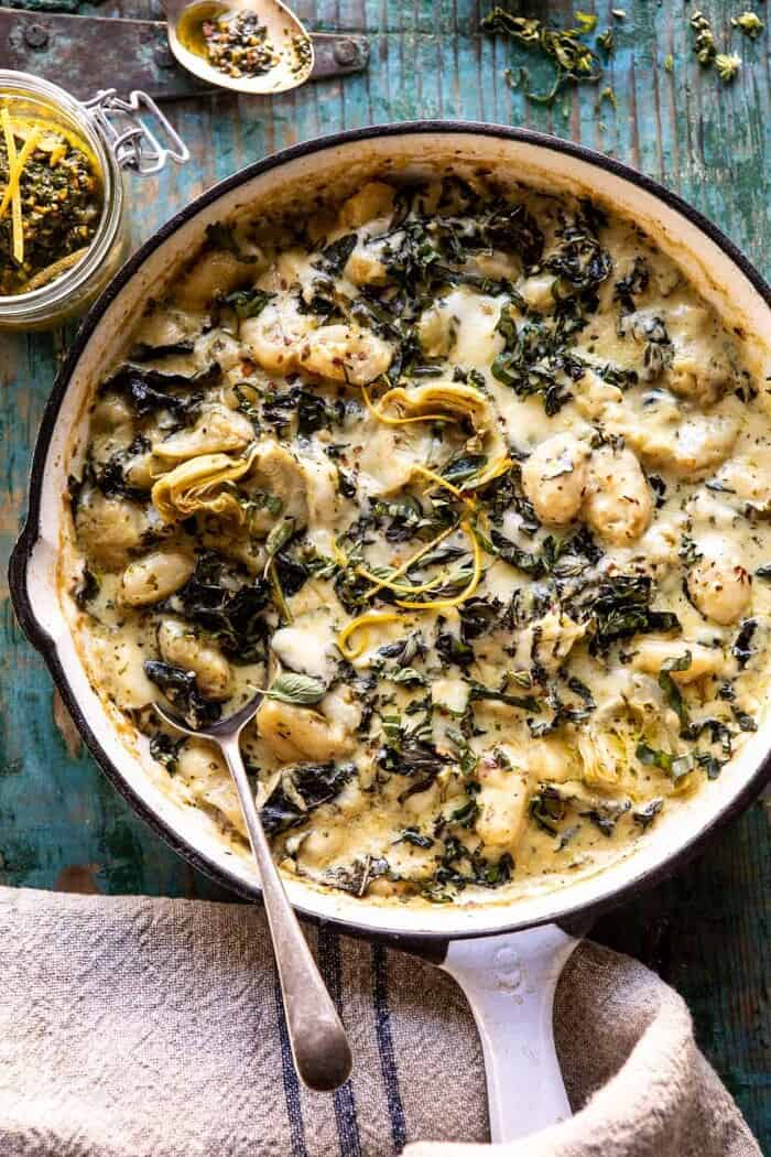 overhead photo of Skillet Baked Creamy Pesto Spinach and Artichoke Gnocchi