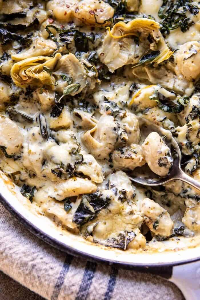 overhead close up photo of Skillet Baked Creamy Pesto Spinach and Artichoke Gnocchi