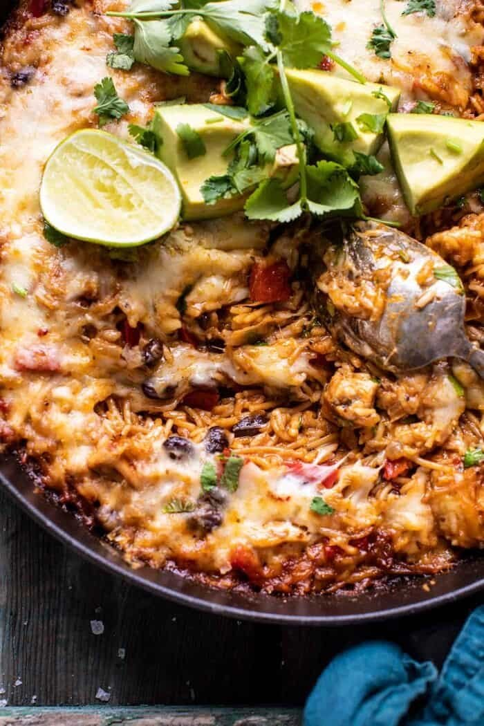 overhead close up photo of One Skillet Cheesy Cuban Chicken Rice Bake with cheese melted and spoon in skillet pulling up the cheese