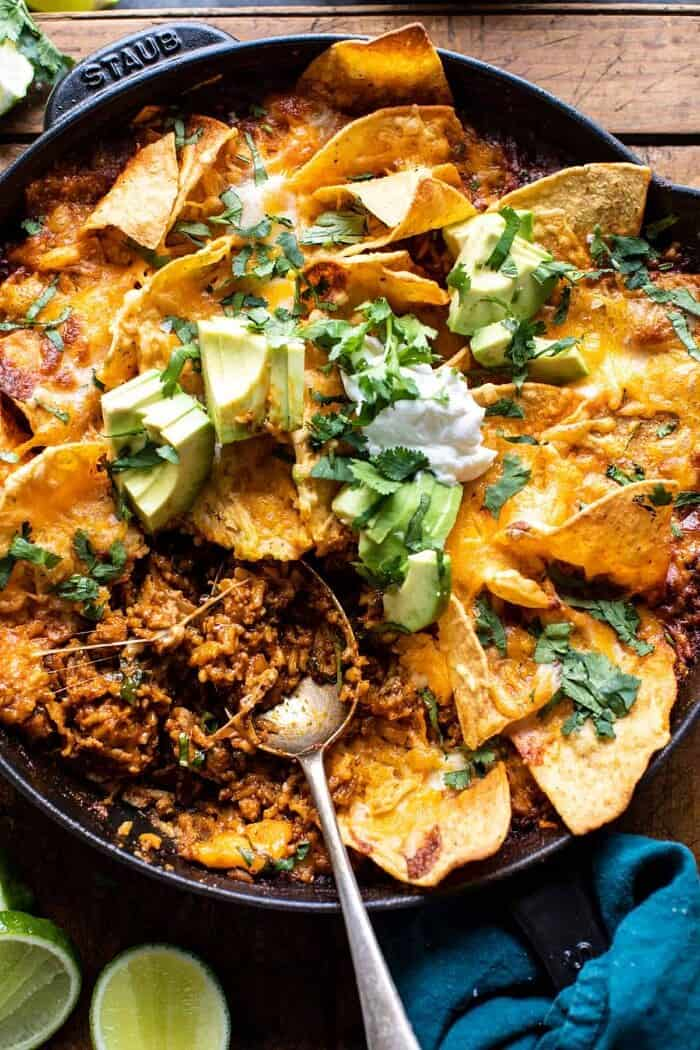 photo of One Skillet Saucy Chicken Tortilla Enchilada Rice Bake with spoon in skillet pulling up the rice to serve