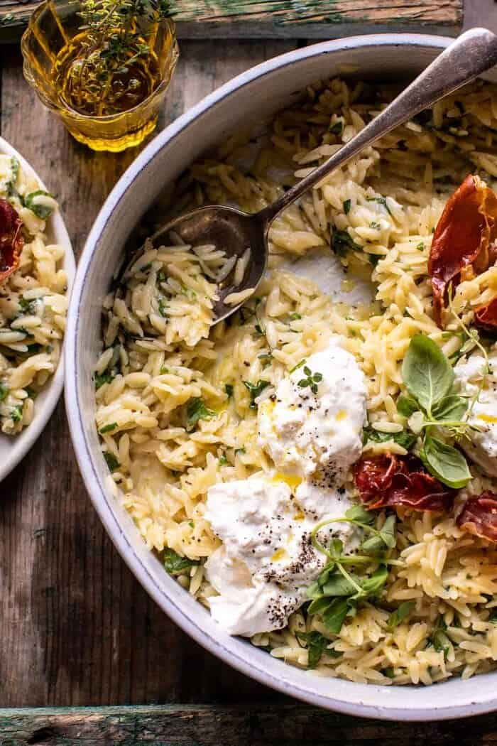 overhead photo fo 20 Minute Orzo Carbonara with Crispy Prosciutto and Burrata with serving spoon in bowl