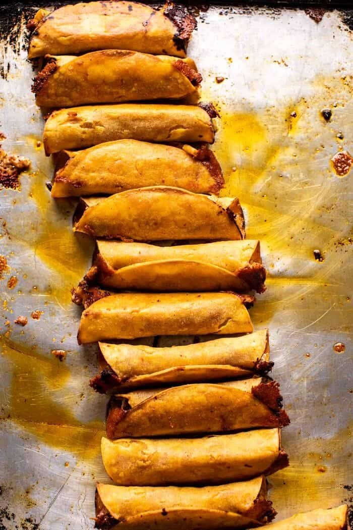 overhead photo of Crispy Chicken Tinga Taquitos after baking on baking sheet