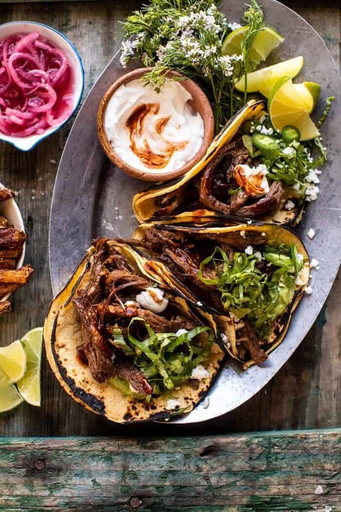 overhead close up photo of Crockpot Carne Asada Tacos with Cilantro Lime Garlic Sauce