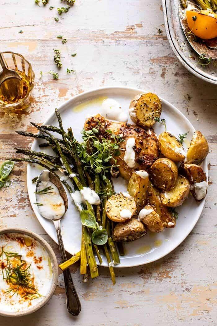 overhead photo of Sheet Pan Lemon Rosemary Dijon Chicken and Potatoes with Feta Goddess Sauce on serving plate