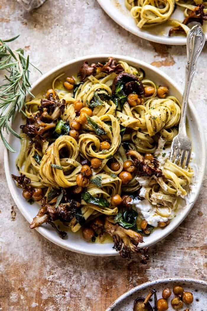 overhead photo of Slow Roasted Mushroom Pasta with Crisp Rosemary Chickpeas with fork twirling pasta on plate