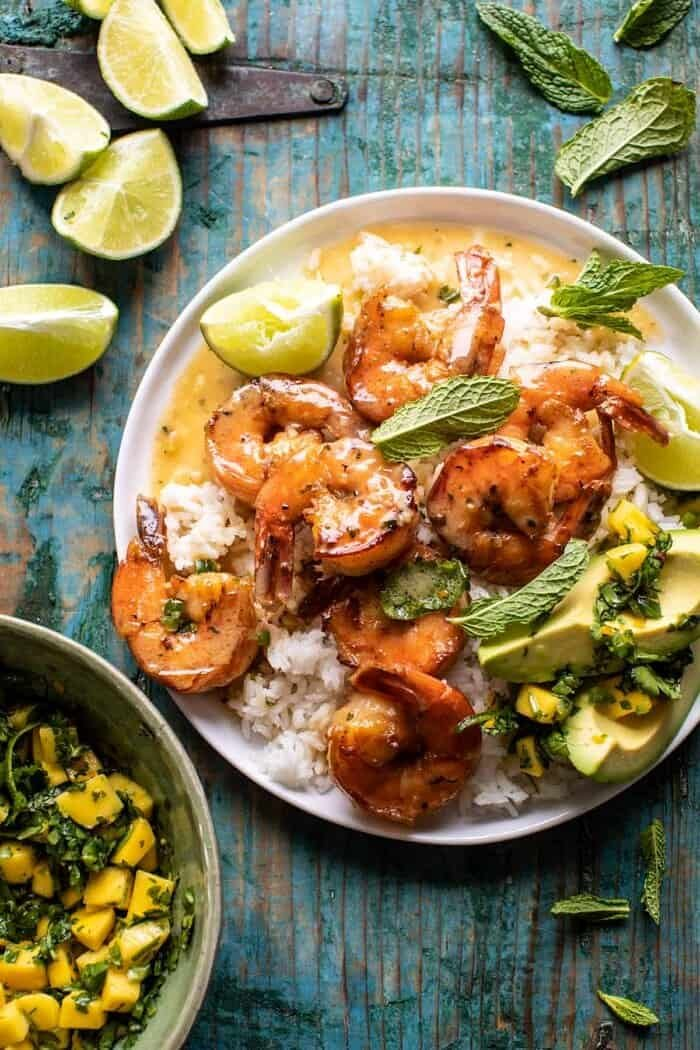 overhead photo of 20 Minute Honey Garlic Butter Shrimp on plate with rice and mangos