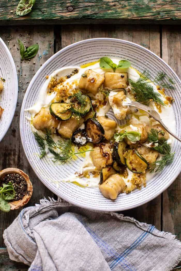 overhead photo of Cauliflower Gnocchi with Crispy Zucchini and Whipped Goat Cheese and fork in bowl with cauliflower gnocchi eaten