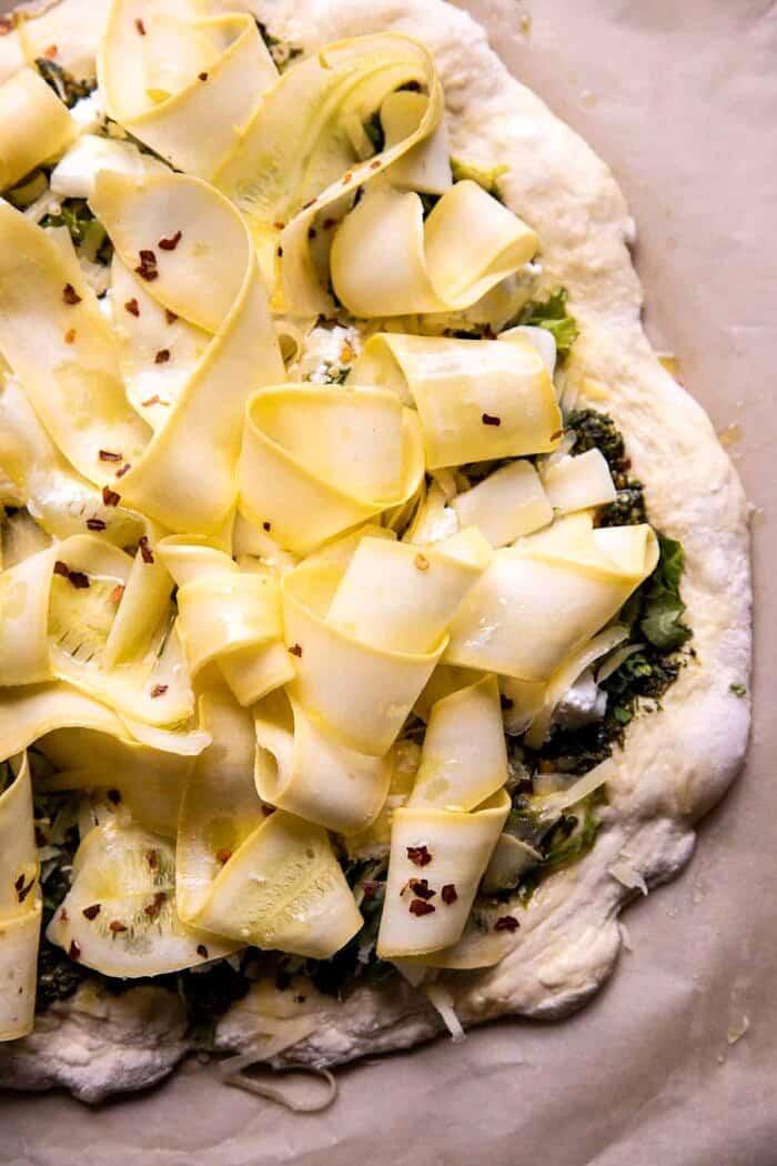 overhead prep photo of Garden Greens Goddess Pizza on baking sheet before baking