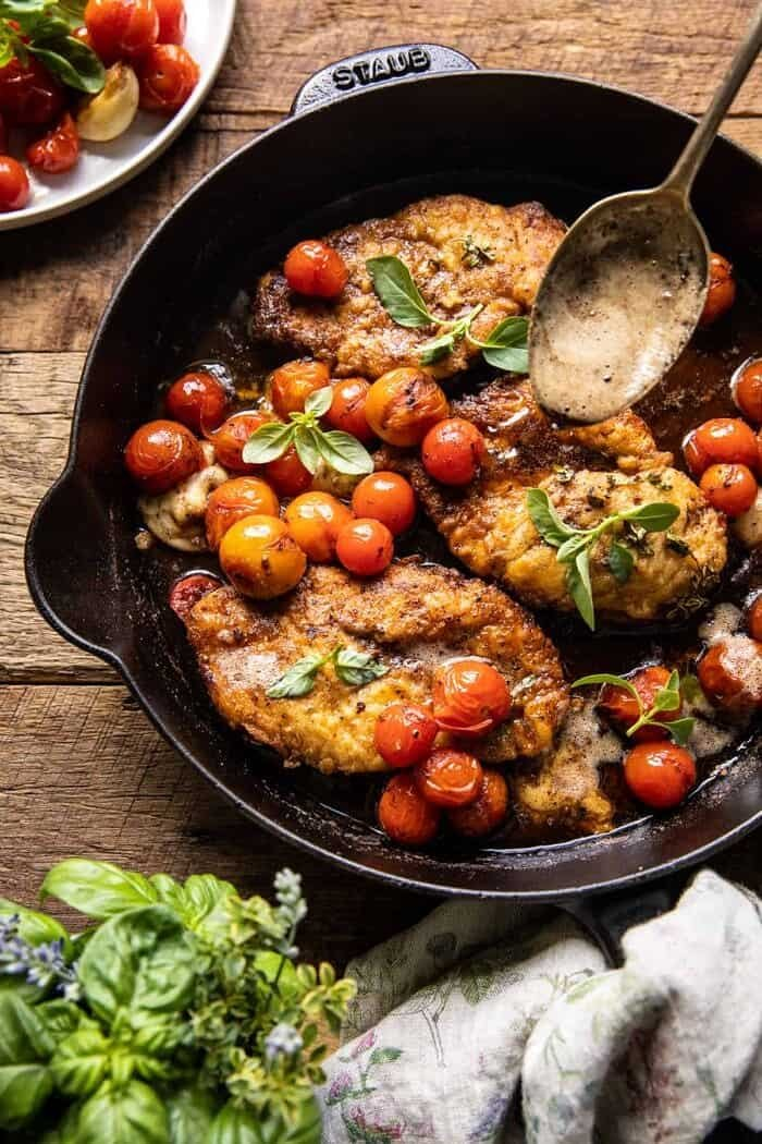 overhead photo of 20 Minute Florentine Butter Chicken with Burst Cherry Tomatoes in skillet with spoon pouring butter over chicken