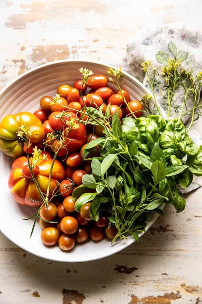 overhead photo of raw tomatoes and herbs in bowl