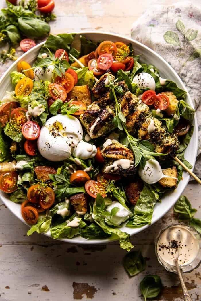 overhead photo of Pesto Chicken Caesar Salad with Tomatoes and Burrata