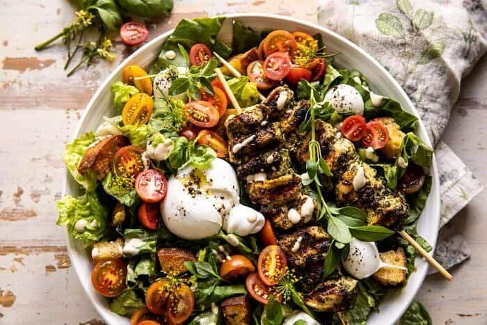 overhead horizontal photo of Pesto Chicken Caesar Salad with Tomatoes and Burrata