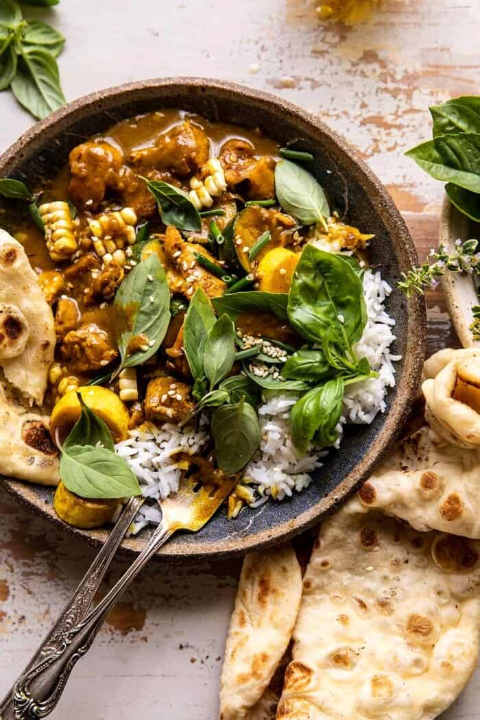 overhead close up photo of Spicy Coconut Basil Chicken Curry with Garden Vegetables with fork in bowl