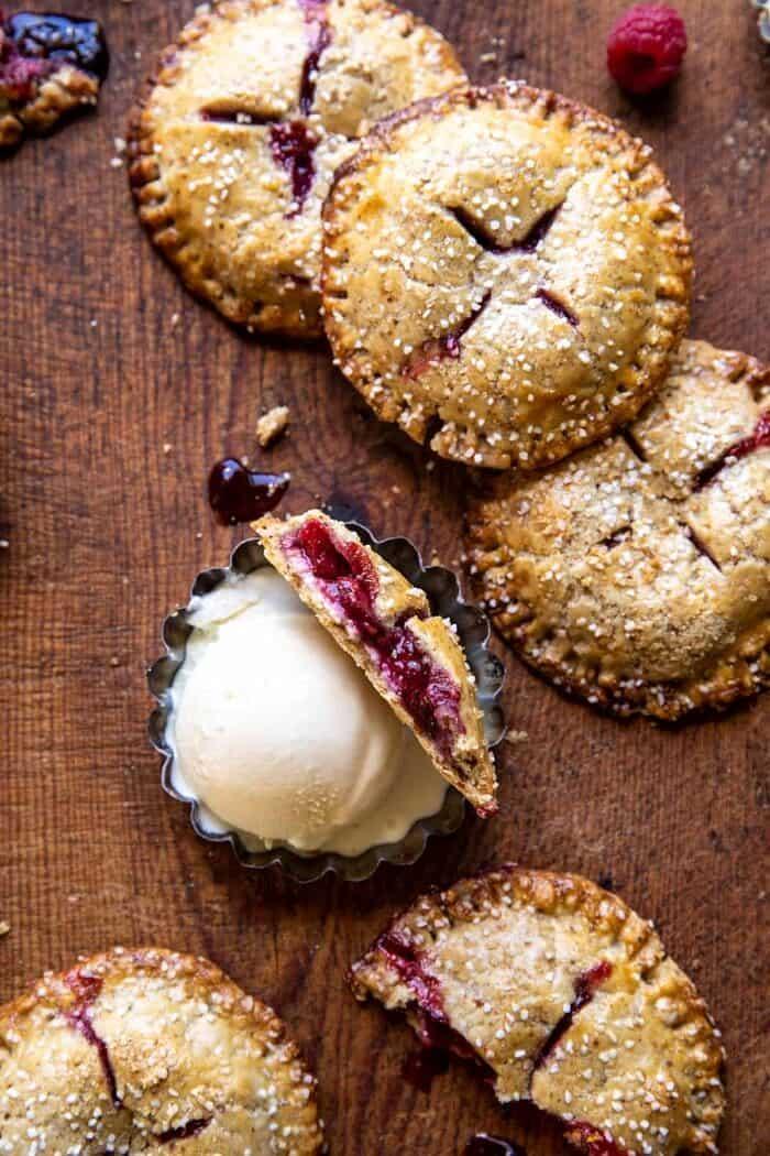 overhead photo of Jammy Raspberry Cream Pretzel Hand Pie broken in half to expose the filling