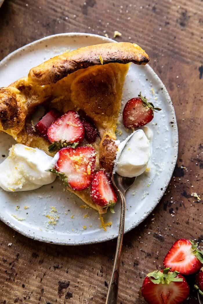 overhead photo of Lemon Strawberry Dutch Baby with Ricotta Cream on serving plate