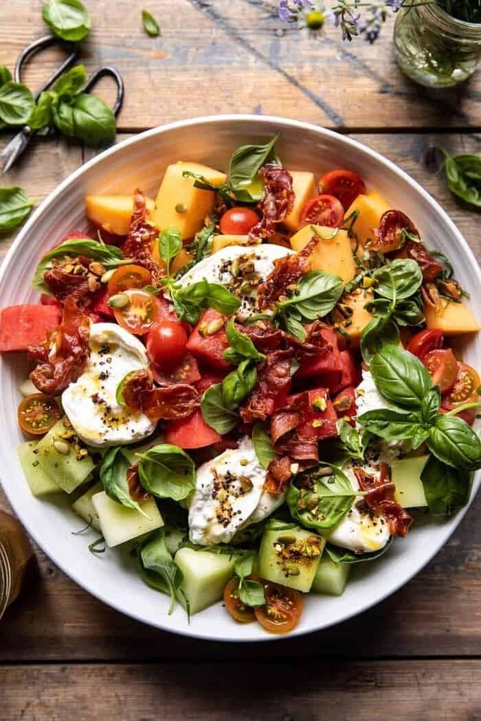 overhead close up photo of Melon Basil Burrata Salad with Crispy Prosciutto