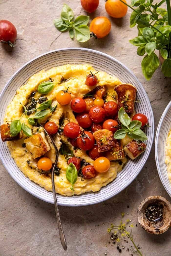 overhead photo of Cherry Tomato Pesto Polenta with Fried Halloumi and fork in serving bowl